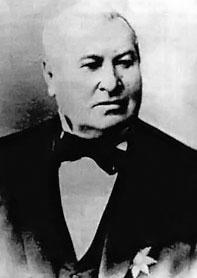 Zdjęcie (popiersie) mężczyzny w średnim lub starszym wieku w czarnym smokingu, białej koszuli i muszce.