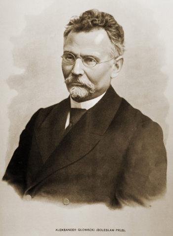 Portret mężczyzny w średnim wieku o krótkiej siwej bródce i siwych wąsach, z lekko kręconymi włosami. Na nosie okulary w cienkiej oprawce.