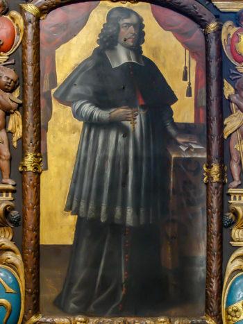 Całopostaciowy portret mężczyzny o długich kręconych włosach w bogatym stroju duchownego, stojącego z dłonią opartą na stoliku. Postać ukazana na złotym tle.
