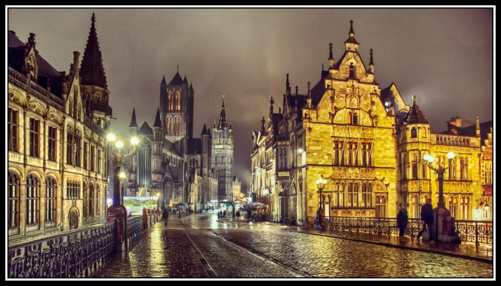 Nocny widok na fragment starego miasta w Gandawie. Wilgotna po deszczu brukowana uliczka lśni w blasku latarni i lamp oświetlających zabytkowe budowle. Ulica otwiera się na widoczną na drugim planie gotycką katedrę.