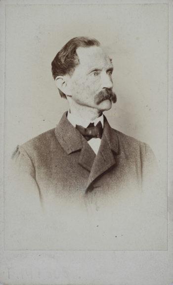 Portret (popiersie) raczej szczupłego starszego mężczyzny z włosami zaczesanymi do tyłu, z sumiastymi wąsami, ubranego w płaszcz (?), spod którego wystaje biała koszula oraz czarna mucha.
