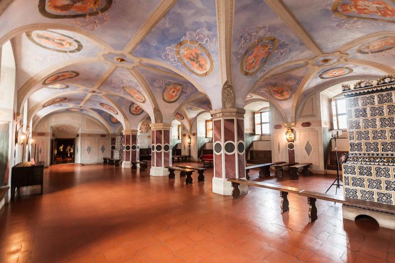 Obszerne pomieszczenie na parterze Zamku Królewskiego z wysoko osadzonymi oknami i renesansowym sklepieniem wspartym na trzech filarach i pokrytym freskiem heraldycznym. Po prawej widoczny piec kaflowy.