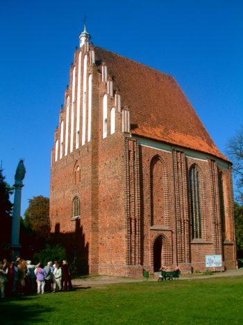 Widok na niewielką, jednonawową gotycką świątynię z czerwonej cegły z wysokim szczytem.