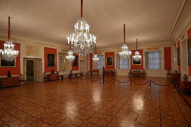 Pusta sala z dużymi oknami i płaskim sufitem, oświetlona przez sześć okazałych, kryształowych żyrandoli. Na ścianach między drzwiami i oknami obrazy z portretami