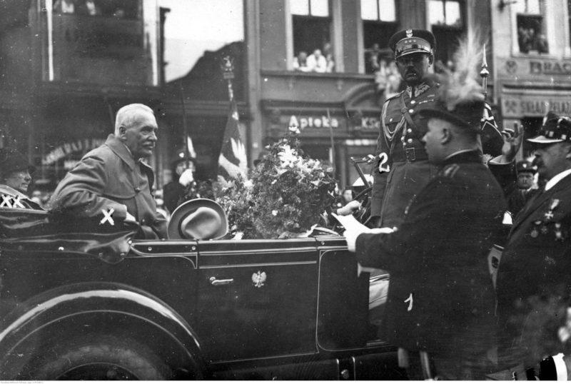 Prezydent Ignacy Mościcki na tylnym siedzeniu kabrioletu ze złożonym dachem. Z przodu samochodu stoi żołnierz w mundurze. Przed drzwiami samochodu mężczyzna z kartką papieru i w kapeluszu z piórami wygłasza powitanie.