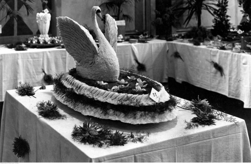 Na duży stole stoi owalny tort (?) z dużym białym łabędziem z podniesionymi skrzydłami. W tle inne stoły z bliżej nieokreślonymi specjałami.