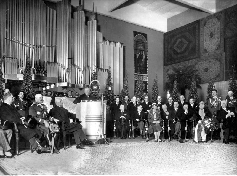 Grupa ludzi na krzesłach siedzi w lekkim łuku twarzami do sali. Między nimi na środku podium do przemówień, na którym stoi mężczyzna. W tle okazałe organy.