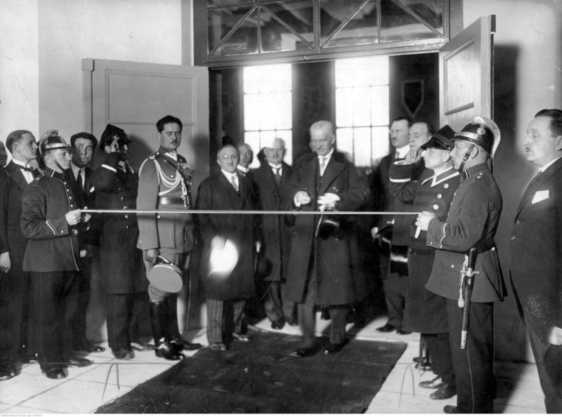 Grupa ludzi w drzwiach. Dwie osoby w mundurach trzymają przed drzwiami wstęgę, a mężyczna w płaszczu na środku szykuje się do jej przecięcia.