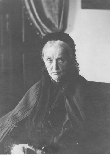 Fotografia portretowa starszej kobiety o poważnym spojrzeniu siedzącej na fotelu, ubranej w ciemny strój.