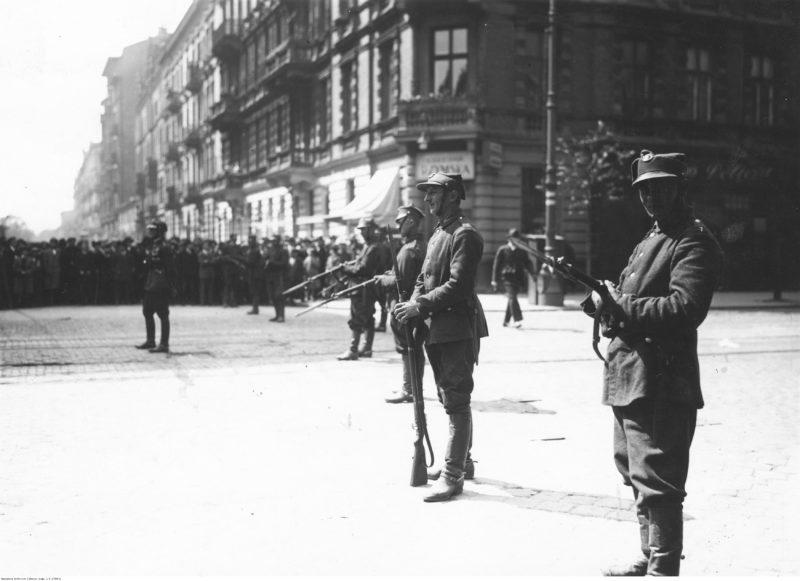 Widok na biegnącą wzdłuż poziomego kadru brukowaną ulicę. Na pierwszym planie widoczni żołnierze stojący luźnym rzędzie w poprzek ulicy, a w tle tłum gapiów.