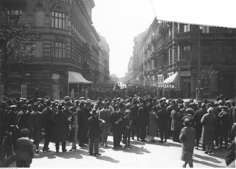 Skrzyżowanie ulic z widocznymi kamienicami przy jednej z nich, naprzeciw fotografa. Po dwóch stronach skrzyżowania w poprzek ulicy stoi tłum gapiów.