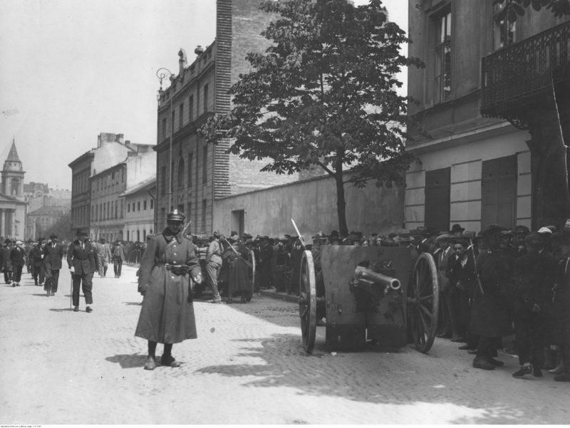 Widok na brukowaną ulicę. Na jej skraju stoją dwa działa polowe obsadzone przez żołnierzy i zwrocone w dwie strony. Na chodniku obok tłum gapiów.