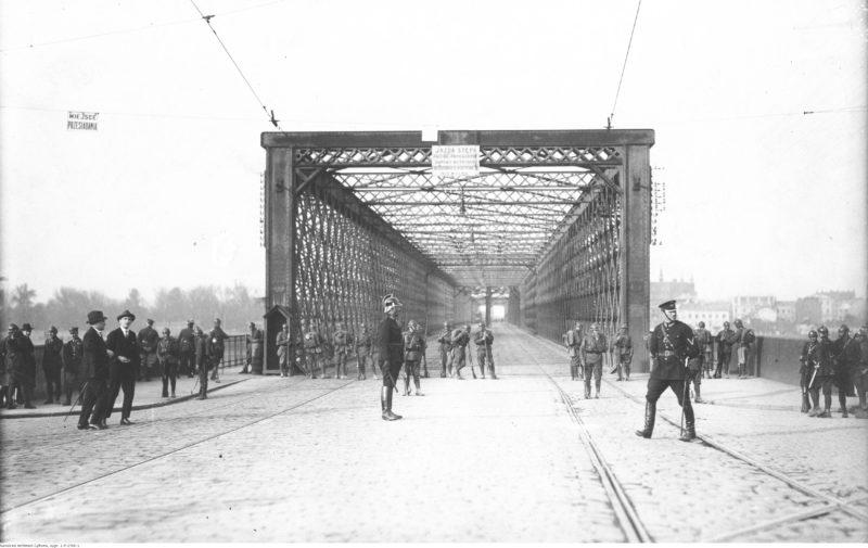 Szerokie ujęcie wejścia na Most Kierbedzia. Widoczna kratownica ponad mostem, kilku policjantów oraz żołnierze stojący w luźnym rzędzie przy wejściu.