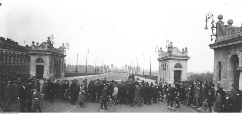 Tłum rozciągnięty w poprzek wjazdu na Most Poniatowskiego z widocznymi charakterystycznymi wieżycami. Za tłumem rozciąga się pusty most, po którym jedzie jeden samochód.