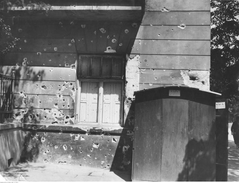 Parter kamienicy z oknem zasłoniętym okiennicami. W ścianie widoczne liczne otwory po kulach, a w niektórych miejscach spore odpryski kamienia powstałe w czasie ostrzału.