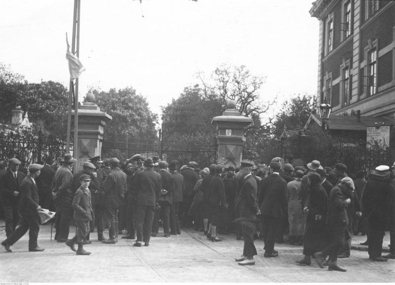 Grupa ludzi rozciągnięta wzdłuż ozdobnego metalowego ogrodzenia z bramą. Po prawej za ogrodzeniem widoczne okna dwupiętrowego budynku.