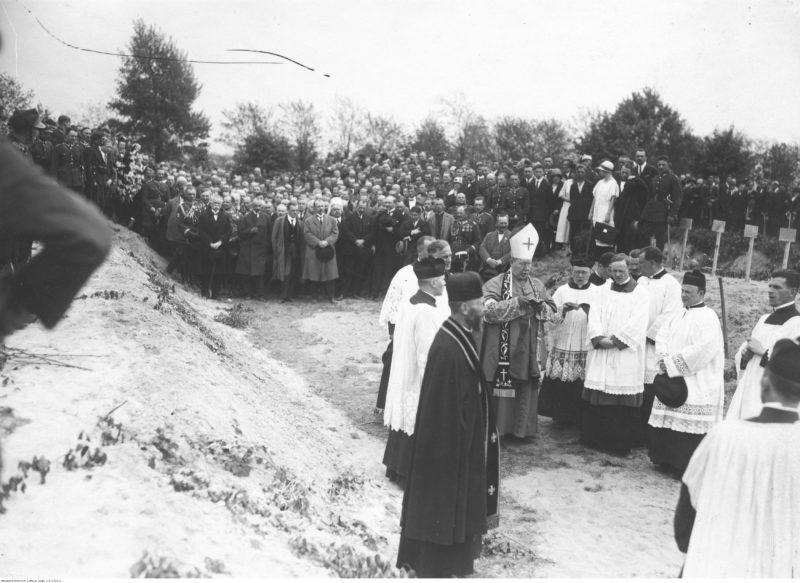 Na pierwszym planie grupa duchownych skupiona wokół biskupa w infule. na drugim planie tłum stojący w poprzek zdjęcia.