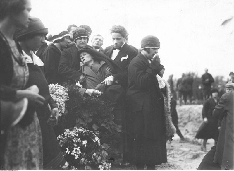Grupa żałobników stojąca nad grobem z wieńcami kwiatów. Na wprost fotografa mężczyzna i kobieta podtrzymują omdlałą kobietę.