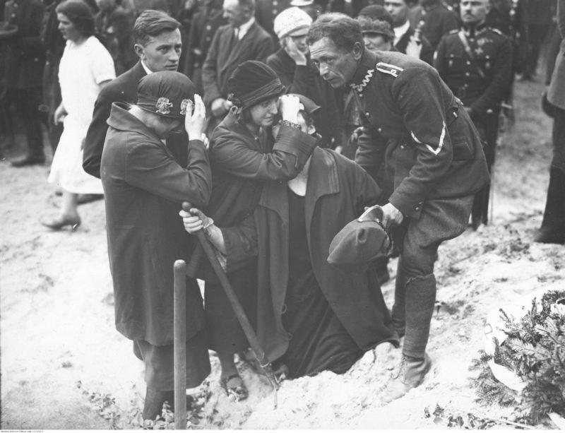 Na pierwszym planie pięcioro żałobników. Jedna z kobiet oraz mężczyzna w mundurze wojskowym podtrzymują omdlewającą kobietę trzymającą trzonek łopaty. Obok stoi jeszcze młody mężczyzna i młoda kobieta z pochyloną głową.