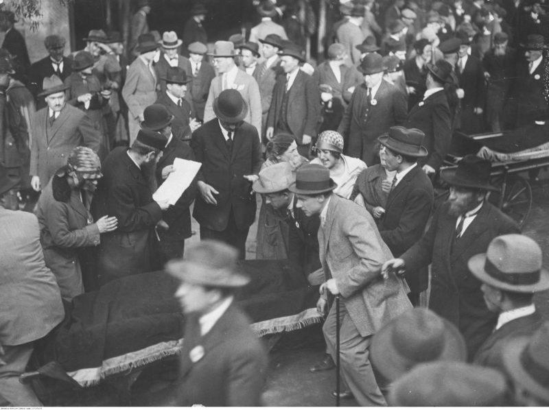 Kilkoro mężczyzn prowadzi wózek z ciałem zmarłego przykryte ciemnym całunem. Za nimi kolejny taki wózek. Dookola grupy żałobników, w centrum kadru obok wózka z ciałem rabin pochylony nad kartką papieru. Obok zrozpaczona kobieta wyrywa się w stronę ciała.