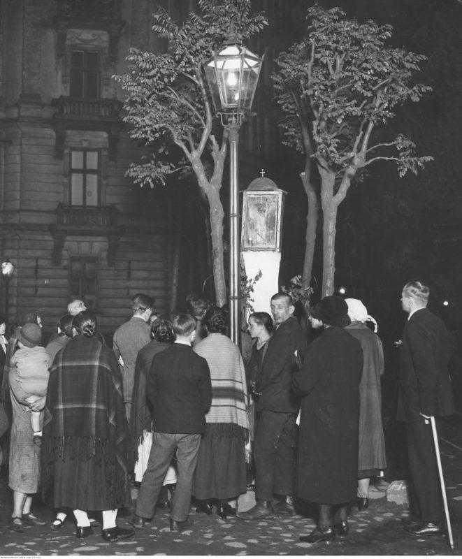 Noc. Na słupie obok ulicznej latarni widoczna niewielka kapliczka, wokół której stoi grupa ludzi zwrócona do fotografa plecami. W tle dwa drzewa i kamienica.