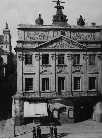 Widoka na fasadę Pałacu Działyńskich w Poznaniu: dużej, barokowo-klasycystycznej kamienicy o wysokości dwóch pięter i szerokości pięciu okien. Fasada podzielona pilastrami w porządku korynckim, zwieńczona wysoką attyką z tympanonem z herbem działyńskich. Na szczycie attyki rzeźba przedstawiająca dużego ptaka: pelikana.