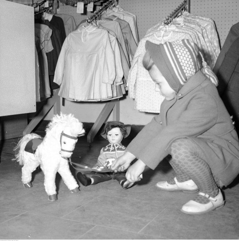 Fragment wnęrza sklepu. Na pierwszym planie widoczna dziewczynka bawiąca się zabawkami. W głębi wieszaki z odzieżą dziecięcą.