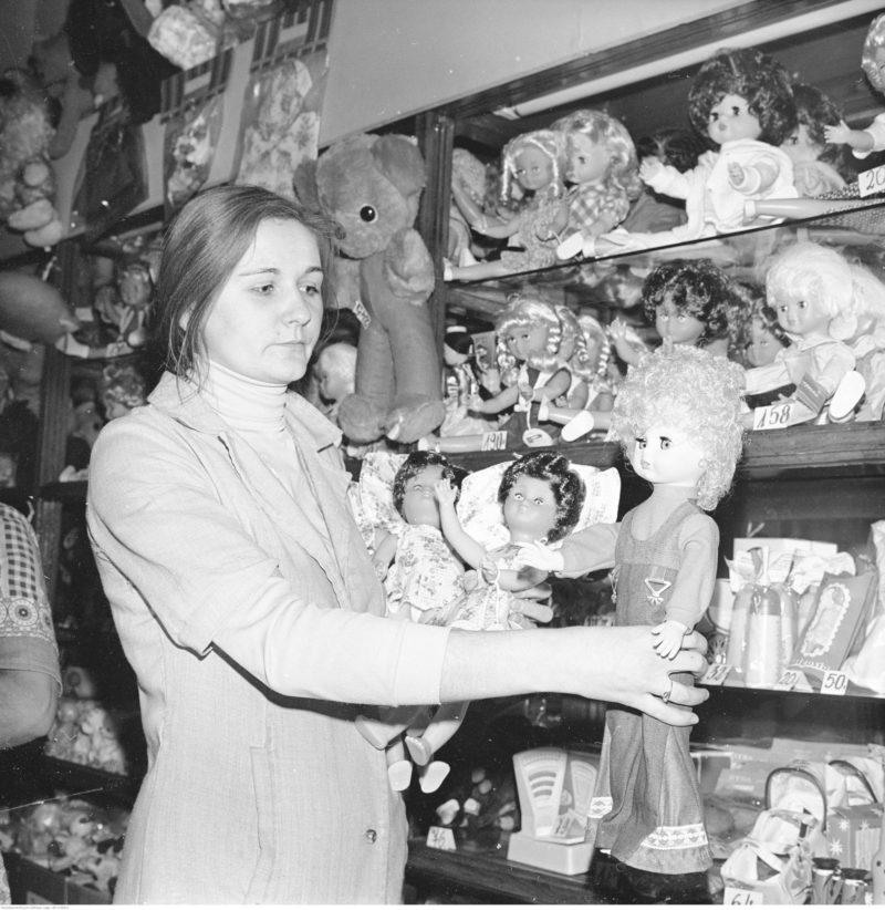 Ekspedientka przy półkach z zabawkami, trzyma w wyciągniętych rękach dużą lalkę.