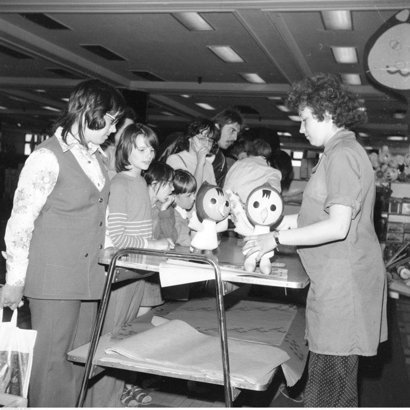 Stoisko z zabawkami. Ekspedientka prezentuje klientom dmuchane zabawki. Widoczne dzieci.