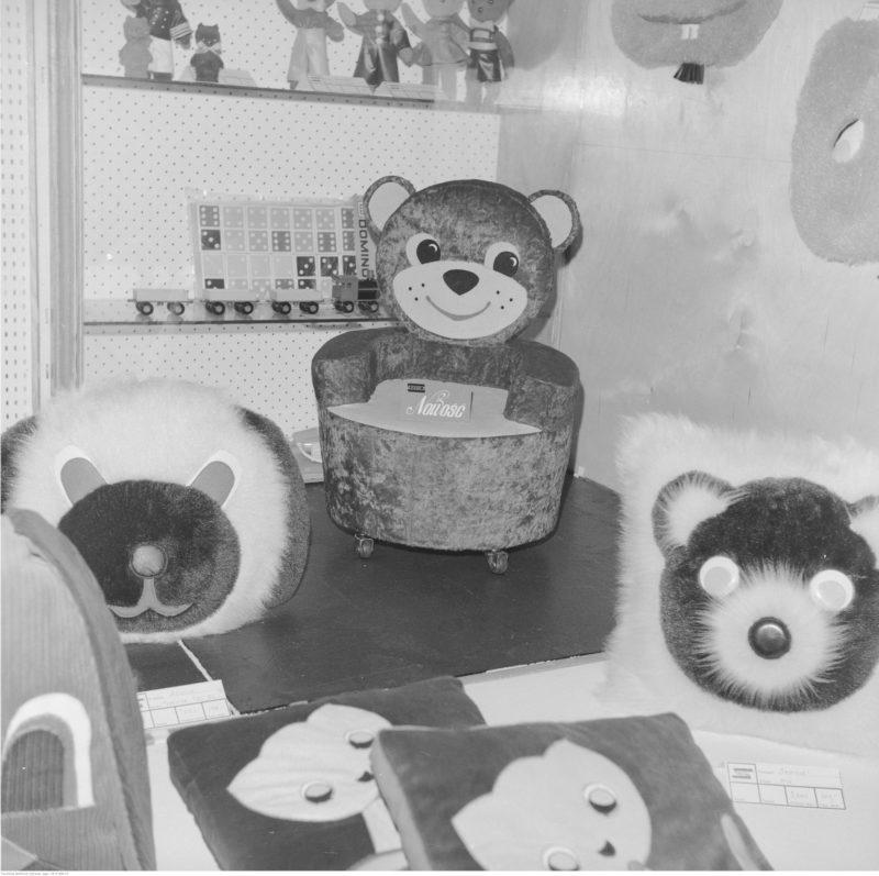 Ekspozycja zabawek. Na pierwszym planie poduszki w kszatałcie zierzaków i fotelik na kółkach w kształcie misia produkcji Spółdzielni Pracy w Kwidzynie.