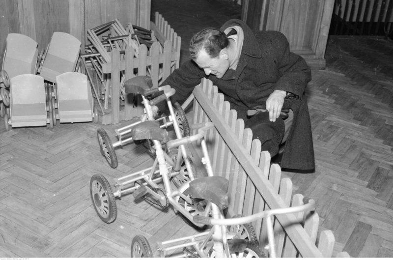Mężczyzna oglądający trzykołowy rowerek dziecięcy.
