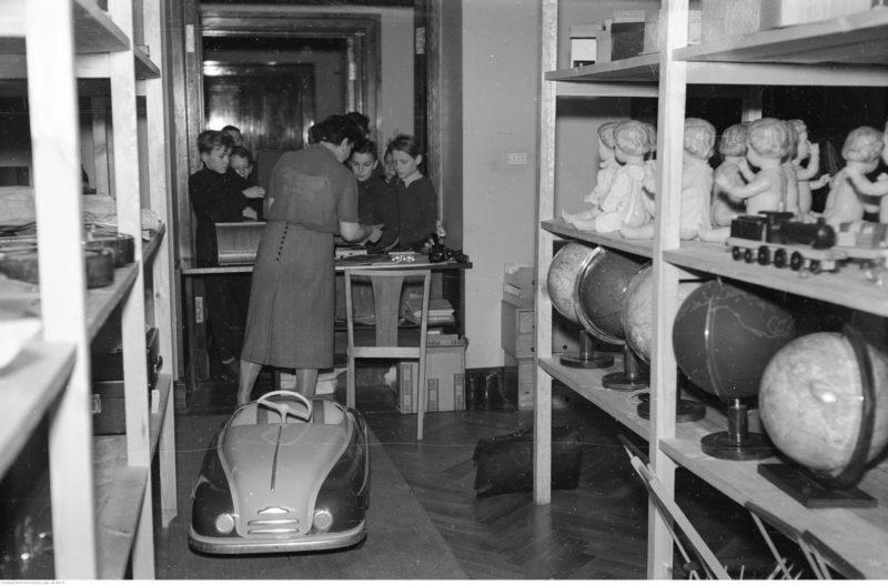 Na półkach widoczne lalki oraz globusy. Na podłodze stoi samochód na pedały.