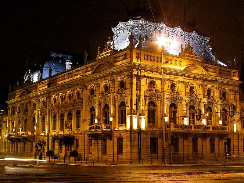 Nocne ujęcie na oświetlony eklektyczny pałac z wysokimi mansardowymi dachami