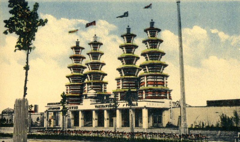 Kolorowana fotografia z widokiem na cztery futurystyczne wierze górujące w jednym rzędzie nad pawilonem wystawienniczym.
