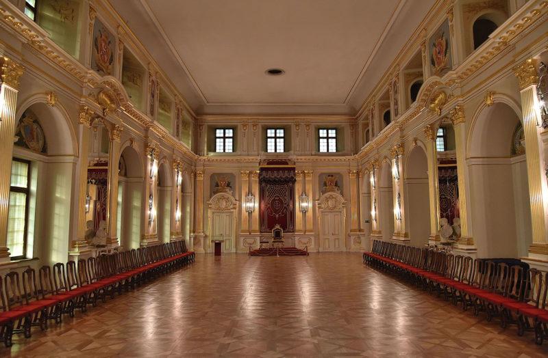 Obszerna, długa sala z wysokimi oknami i płaskim sklepieniem, zdobiona złoceniami i pilastrami. U szczytu tron królewski.