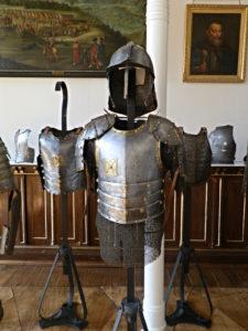 Napierśnik husarski z naramiennikami, szyszakiem i kolczugą pod spodem na stojaku w sali muzealnej. W tle inne zbiory i obrazy na ścianach.