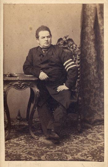 Postawny mężczyzna w średnim wieku w dwurzędowym płaszczu siedzi na rzeźbionym krześle, opierając prawą rękę na małym okrągłym, również rzeźbionym stoliku. Na podłodze dywan, po lewej stronie mężczyzny kadr zamyka zwisająca gdzieś z góry zasłona.