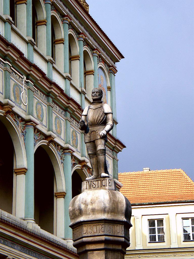 Czarna figurka rycerza wieńcząca poznański pręgierz. W tle widoczny fragment fasady ratusza.