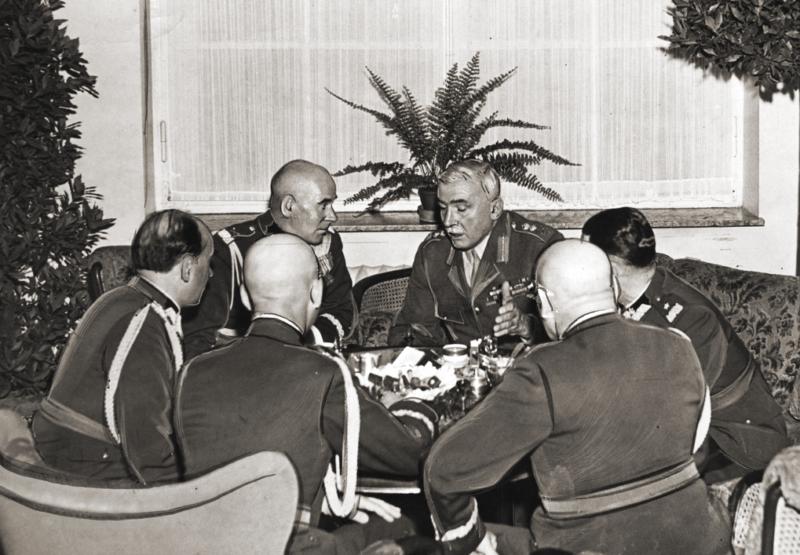 Sześciu mężczyzn w mundurach wojskowych rozmawia dookoła niewielkiego okrągłego stolika.