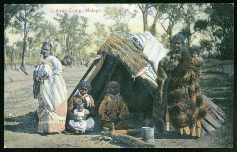 Kolorowe zdjęcie przedstawiające grupę ciemnoskórych kobiet na tle buszu. Dwie z nich stoją po dwóch stronach szałasu, przed którym siedzą dwie kolejne. Trzy z nich trzymają w rękach małe dzieci. Wszystkie noszą europejskie ubrania, a kobieta po prawej dodatkowo ma na sobie brązowe futro zwierzęce.