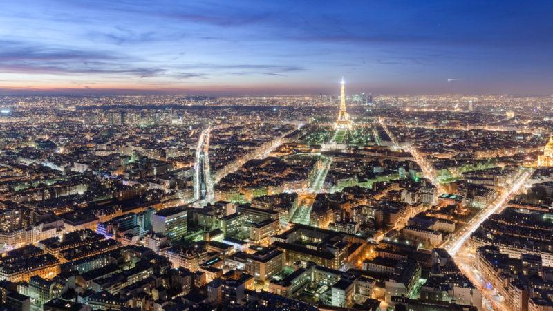 Widok z lotu ptaka na Paryż o zmroku. W jednej trzeciej obrazu widoczna linia horyzontu z wąskim fragmentem czerwonego nieba rozświetlonymi ostatnimi promieniami słońca. Wyraźnie widoczne światła domów oraz latarni wzdłuż ulic, a także Wieża Eiffla.