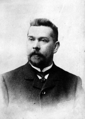 Czarno-biały portret (popiersie) mężczyzny mającego ok. 35 lat, z krótką brodą i wąsami.