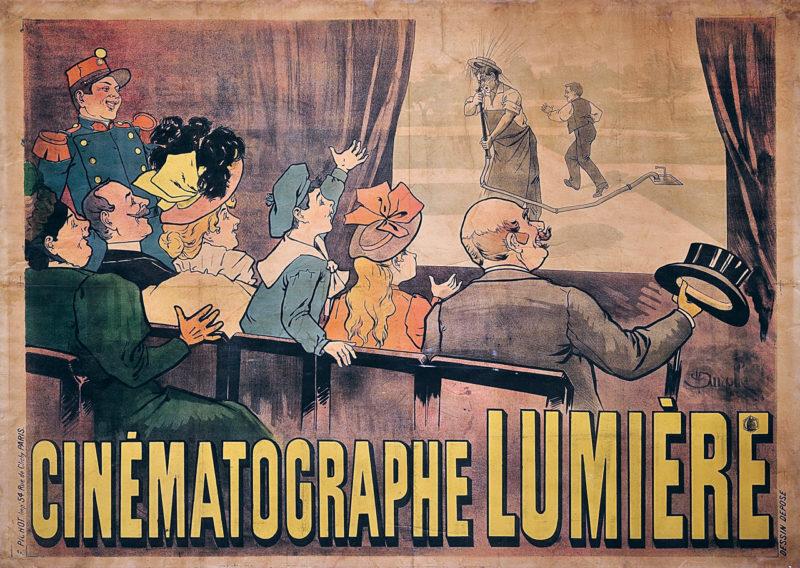 Kolorowy rysunek przedstawiający od tyłu sześcioro osób na sali kinowej, żywo reagujących na widoczną na ekranie scenę, w której woda z węża ogrodowego tryska w twarz ogrodnikowi. Za nim ucieka psotnik, który odkręcił zawór.
