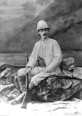 Portret mężczyzny w jasnym stroju tropikalnym, w czapce, siedzącego na kamieniach, z karabinem opartym na nodze.