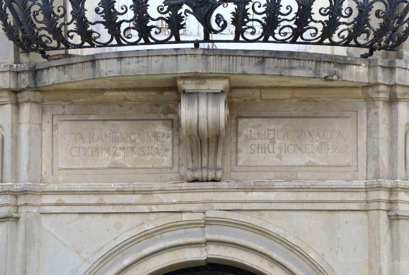 """Na płycie z piaskowca umieszczonej nad portalem wejściowym, a pod balkonem, widnieje napis: """"Ta kamienica niegdy Prażmowska libertowana constitutione A.D. 1667""""."""