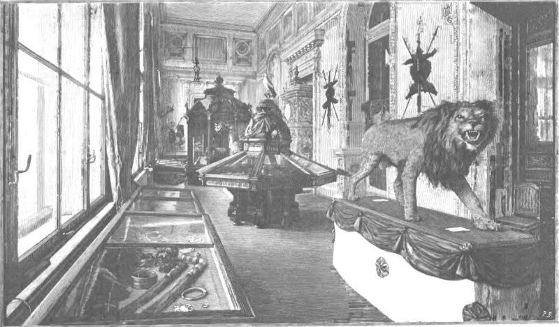 Podłużna sala w pałacowym wnętrzu z dużymi oknami. Pod oknami oraz na środku sali stoją gabloty z ekspnatami. Na pierwszym planie widoczny wypchany lew z otwartym pyskiem.