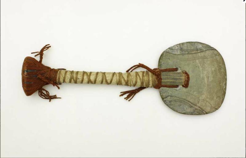Siekierka ceremonialna z ostrzem w kształcie dysku wykonanym z jadeitu, osadzonym na wpust w drewnianym trzonie. W ostrzu wywiercone dwa otwory, przez które przewleczono sznur mocujący. Trzon z rękojeścią zwieńczony głowicą, owinięty tapą, tkaniną, opleciony sznurem z włókien roślinnych i wełny.