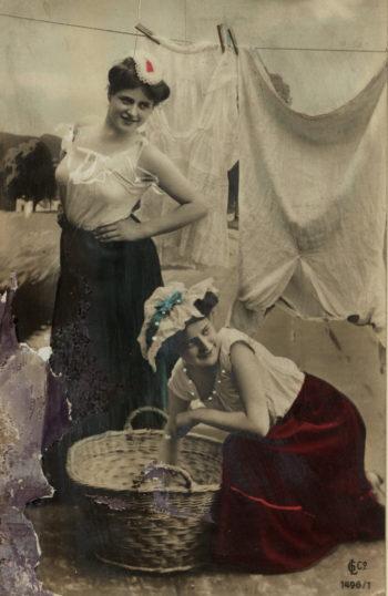 Dwie kobiety w spódnicach i białych koszulach bez rękawów na tle sznura z bielizną. Jedna z nich stoi, druga pochylona jest nad wiklinowym koszem.