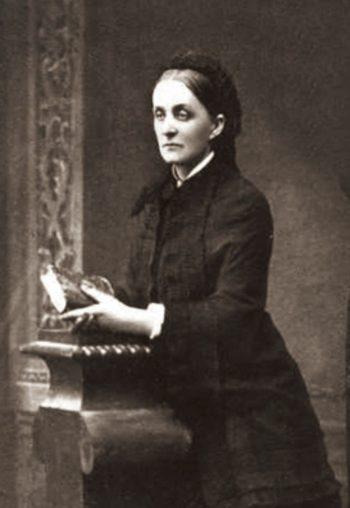 Zdjęcie kobiety w długiej czarnej sukni, z książką w dłoniach opartych na klęczniku.