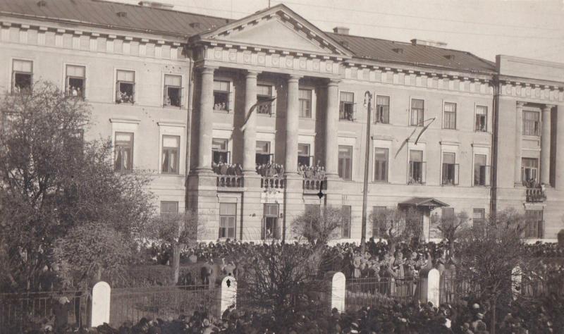 Tłum ludzi przed dużym, trzykondygnacyjnym reprezentacyjnym budynkiem. Na jego balkonie stoi druża grupa ludzi.